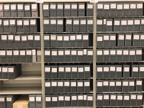 Image of archived catalogs on grey metal shelves