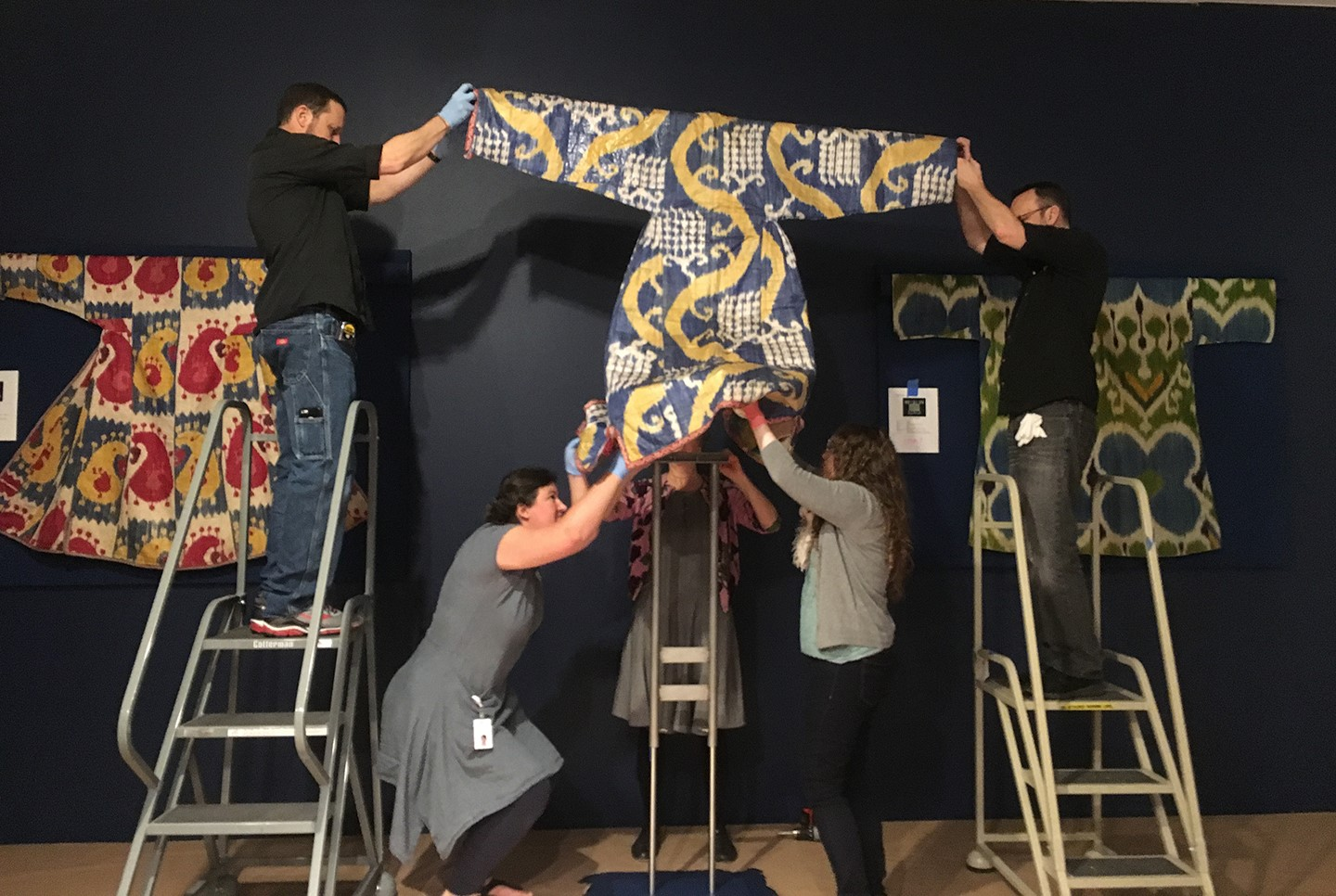 Esther Méthé (back, center) works with MFAH staff to place a woman's robe onto a mount.