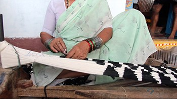 A woman binds yarn in order to create an ikat textile.